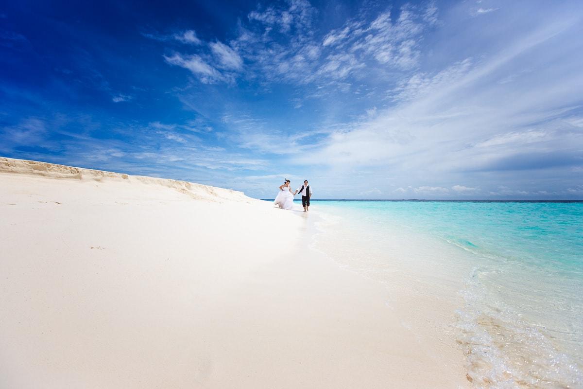 Brautpaar rennt am Strand der Malediven vor freude