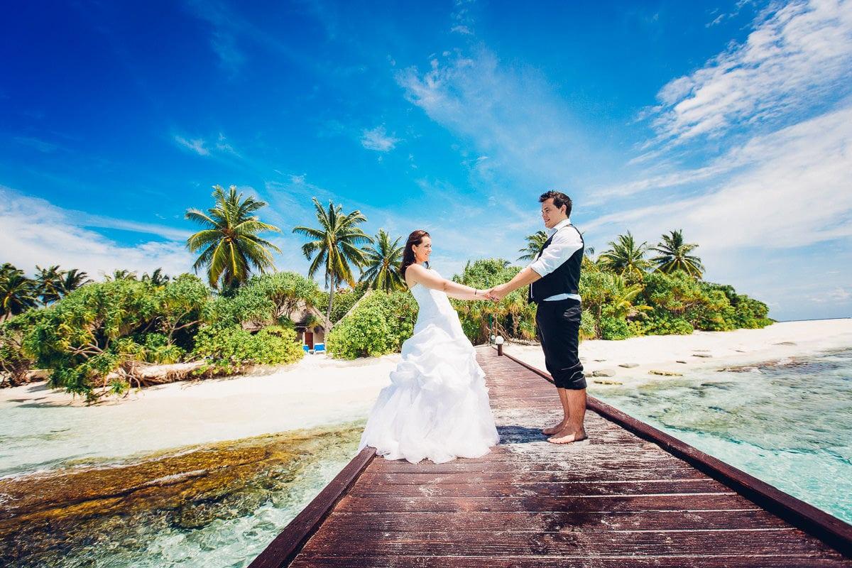 Hochzeitspaar auf einem Steg am Strand